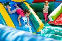 Child Jumping On Colorful Playground Trampoline. Kids Jump In Inflatable Bounce Castle On Kindergarten Birthday Party Activity And Play Center For Young Child. Little Girl Playing Outdoors In Summer