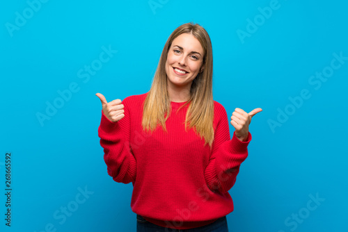 Valokuvatapetti Woman with red sweater over blue wall with thumbs up gesture and smiling