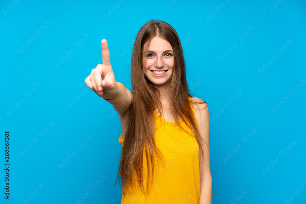 Fototapeta Young woman with long hair over isolated blue wall showing and lifting a finger