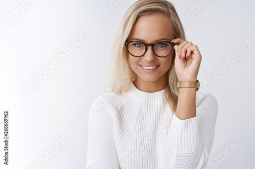 Charming female wants help pick glasses. Portrait of elegant and sensual young blond woman with daring and cheeky smile looking confident touching frames as posing against white background