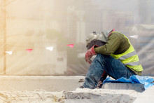 The Tired Construction Worker In The Green Waistcoat And The Red Glove Sitting In The Construction Area
