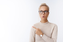 Wow Amazing. Portrait Of Amused And Surprised Creative Young Female Blond Social Blogger Looking Up Pointing Upper Left Corner Folding Lips Impressed And Stunned Of Awesome Idea Over White Background