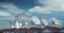The Mast And Various Satellite Dishes And Aerials Of A Huge Military Or Research Ship In The Background, Partly Hidden By A Row Of Houses Of The Same Type With Triangular Roofs In The Foreground