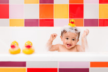 Happy Baby In Bubble Bath With Rubber Duck On Top Of Head