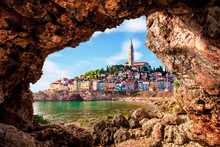 Unusual View With Old Clock Towe In Piran Through A Rock Hole. The Tourist Center Of Slovenia. Popular Tourist Attraction. Wonderful Exciting Places.