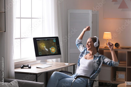 Fotografering Emotional young woman playing video games at home
