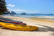Colorful Kayaks On The Beach Of Island In Philippines. Canoe On Coast With Isles And Traditional Philippines Boats On Background. Tropical Vacation And Travel. Active Tourism. Asian Landscape.