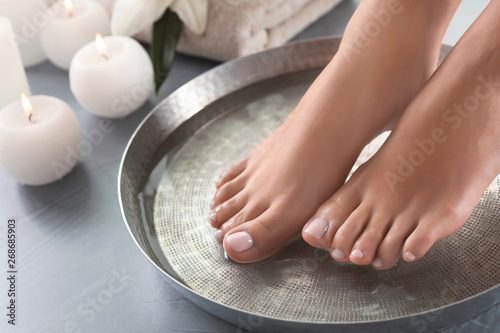 Foto op Plexiglas Spa Closeup view of woman soaking her feet in dish with water on grey floor. Spa treatment