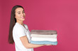 Leinwandbild Motiv Happy young woman holding clean towels on color background, space for text. Laundry day