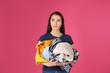 Leinwandbild Motiv Displeased young woman holding pile of dirty laundry on color background