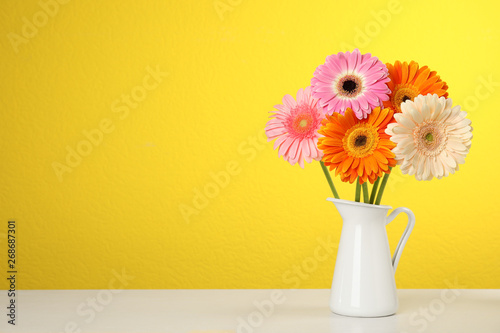 Foto op Canvas Madeliefjes Bouquet of beautiful bright gerbera flowers in vase on table against color background. Space for text