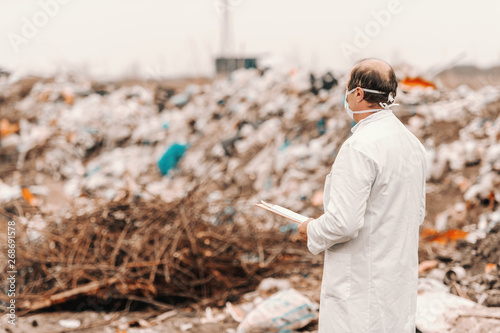 Valokuva Ecologist in white uniform and mask on face holding clipboard, evaluating damage and looking at landfill