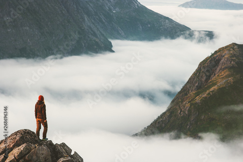 Fotomural Traveler on cliff overlooking mountain clouds alone hiking adventure journey out
