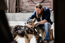 Brutal Man With A Beard Dressed In Casual Clothes Is Sitting On A Stump And Petting A Dog  Next To The Wooden Wall
