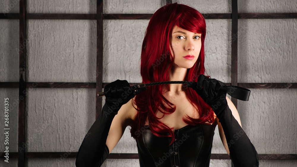 Fototapeta Red-haired girl in a leather corset holds spank.