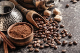 Fototapeta Kawa jest smaczna - Coffee beans in wooden spoon on dark textured background.
