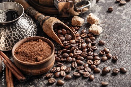 Fotografie, Obraz  Coffee beans in wooden spoon on dark textured background.
