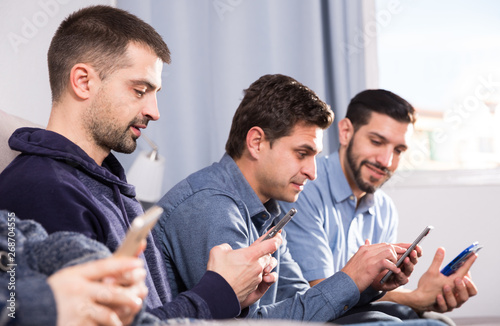 Fotografie, Obraz  Three men with smartphones at home