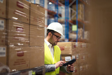 Warehouse Worker Using Bar Code Scanner To Organize Goods Distribution.