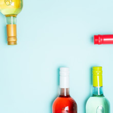 Screw Bottle Foil Caps In Different Bright Colors Of White And Rose Wine Bottles On Blue Background With Copy Space. Minimal Abstract Colorful Mockup Concept Of Alcohol Beverage. Flat Lay.