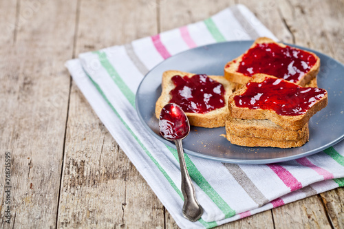 Canvastavla Fresh toasted cereal bread slices with homemade cherry jam and spoon on ceramic plate closeup on linen napkin on rustic wooden table background