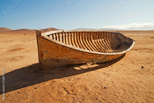 Tuinposter Schip A broken, discarded boat in the desert