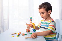 Little Boy Playing With Toy Tools And Building A Vehicle