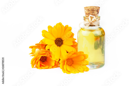 Fotografía  Glass bottle of calendula essential oil with fresh marigold flowers isolated on white background