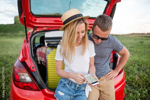 Fotografie, Obraz  Couple looking at the navigation map in the phone sitting in the trunk of the ca