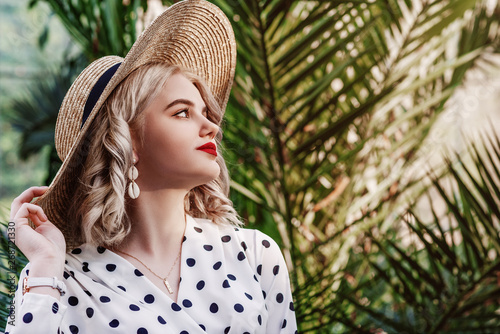 Outdoor close up fashion portrait of young beautiful lady wearing  trendy shell earrings, stylish straw wide brim hat, polka dot blouse, posing in street with palms. Copy, empty space for text