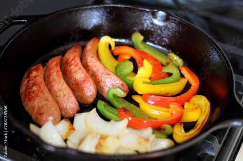 Sausage cooking on the stove in a cast iron skillet with bell peppers and onion.