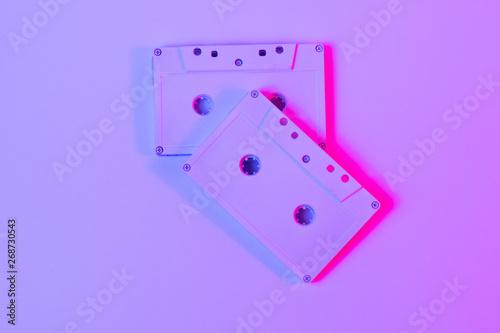 Trendy reviving retro audio cassette tape on pink and green neon light Fototapeta