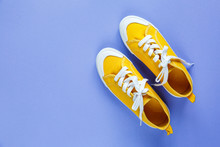 New Pairs Of Yellow  Sneakers On Violet Background With Copy Space. Lifestyle  Sneaker Sport Shoe.