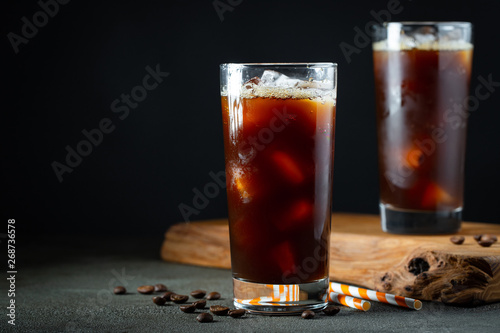 Photo  Ice coffee in a tall glass with cream poured over, ice cubes and beans on a old rustic wooden table