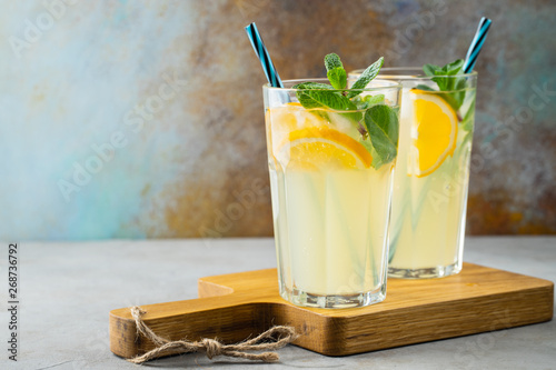 Valokuvatapetti Two glass with lemonade or mojito cocktail with lemon and mint, cold refreshing drink or beverage with ice on rustic blue background