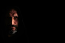 Brutal Man With A Gray Beard In The Hood With Sharp Shadows On A Black Background. Copy Space.