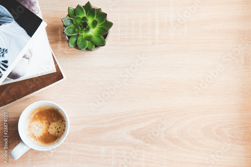 Valokuva  Top view of  books and magazines, cup of coffee and succulent plants over wooden background