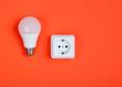 Leinwanddruck Bild - White plastic power socket and LED light bulb on orange background. Minimalism. Top view