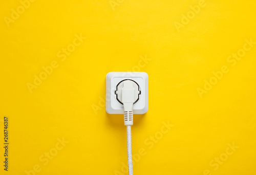 White cable plugged into power outlet on yellow wall background Fototapete