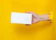 canvas print picture - Female hand holds white box through torn yellow paper. Minimalistic creative fashion concept