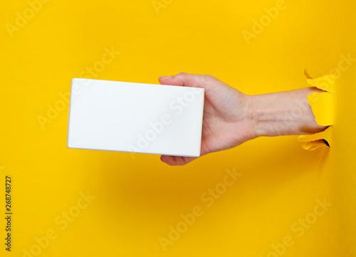 Photo  Female hand holds white box through torn yellow paper