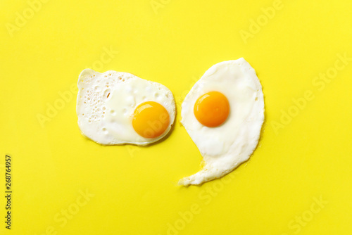 Two fried eggs on yellow paper background. Creative food concept in minimal style. Top view