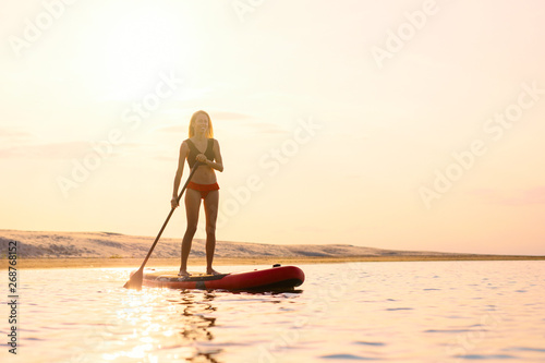 Silhouette of woman standing on paddle board Fotobehang