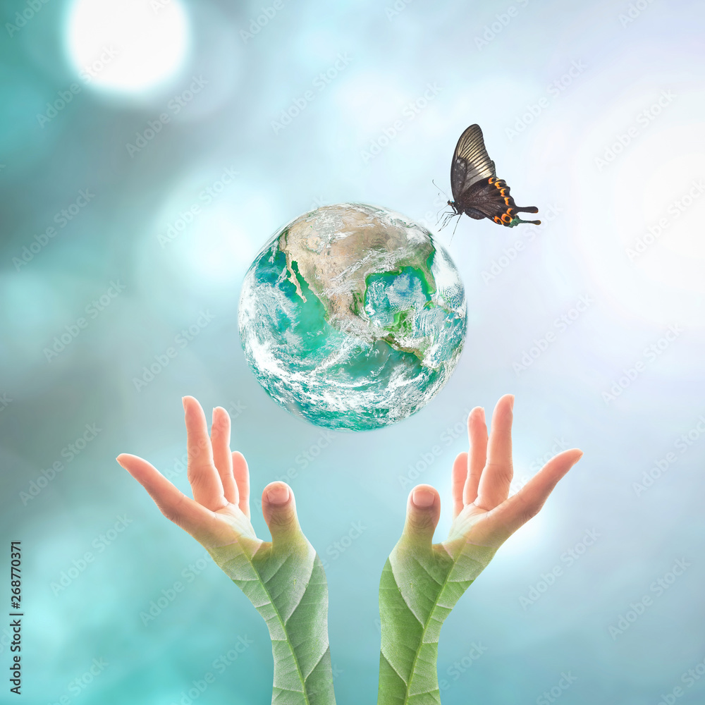 Fototapeta Earth day and go green concept with big green planet on people's hand with tree leaves  : Elements of this image furnished by NASA...