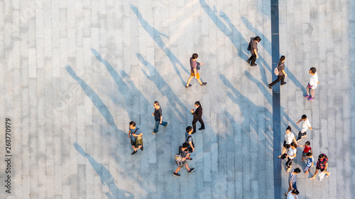plakat group of people walk on across the pedestrian concrete landscape in the city street (Aerial top view)