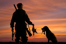 Hunter And His Dog With Prey At Sunset