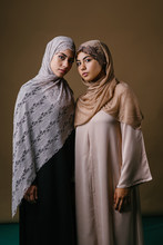 Two Muslim Middle Eastern Sisters In Traditional Dresses And Hijab Head Scarves Stand And Pose For A Portrait Together In A Studio. They Are Both Young, Beautiful, Elegant And Attractive.