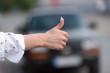 Eine Frau will per Anhalter mit Auto fahren