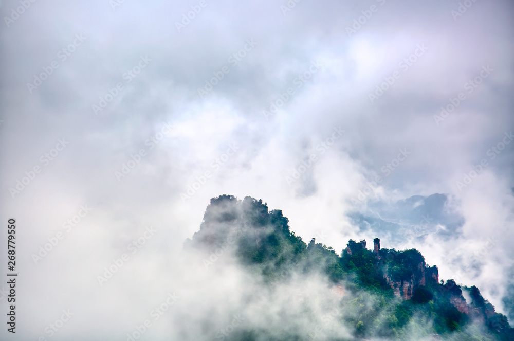 Zhangjiajie National park. Famous tourist attraction in Wulingyuan, Hunan, China. Amazing natural landscape with stone pillars quartz mountains in fog and clouds