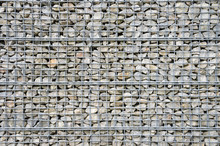 Abstract Architectural Background Of Rough Retaining Wall Made From Rocks In Steel Cage Gabion Baskets